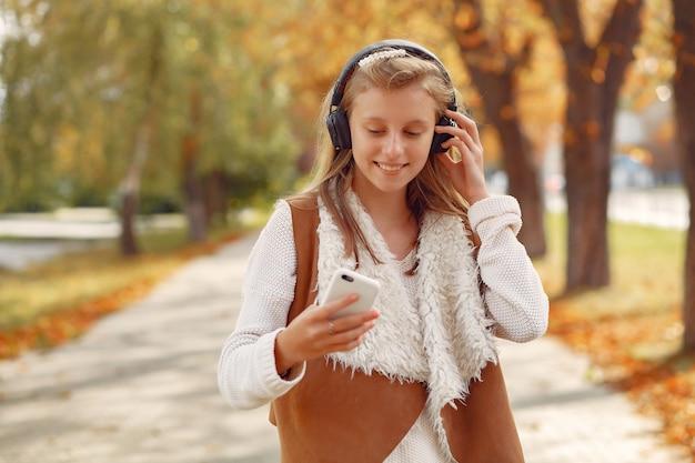 Fille élégante et élégante dans un parc en automne Photo gratuit
