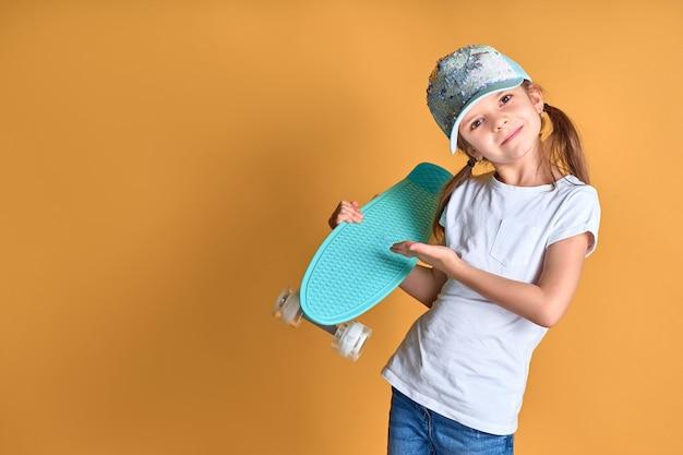 Fille élégante Portant Un T-shirt Blanc, Un Jean Bleu Et Une Casquette Verte, Tenant Une Planche à Roulettes Sur Fond Jaune Photo Premium
