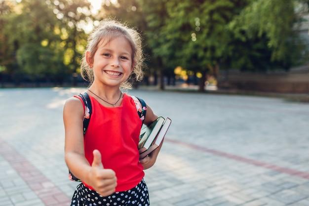 Fille élève heureux portant sac à dos et tenant des livres Photo Premium