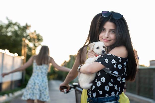 Fille embrassant un chien mignon et regardant une caméra Photo gratuit