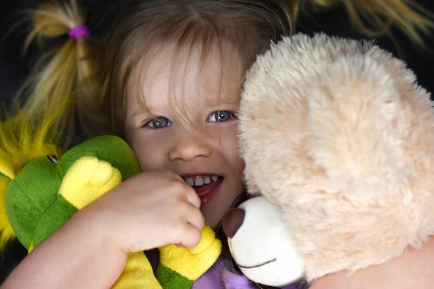 Fille embrasse des jouets en peluche et rit Photo Premium