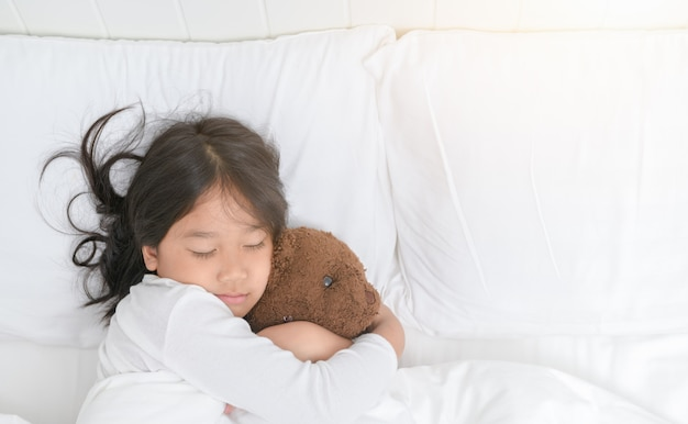 Fille embrasse un ours en peluche pendant qu'il dort dans son lit Photo Premium