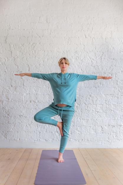 Fille enceinte dans un costume de sport bleu se dresse dans la pose de yoga, portrait de pleine longueur Photo Premium
