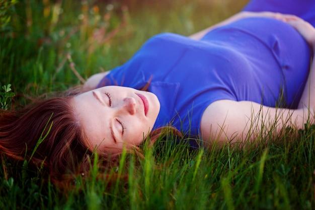 Fille enceinte est allongée dans l'herbe et rêve de sa grossesse Photo Premium