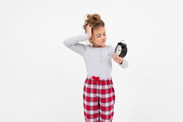 Fille Endormie En Pyjama Vient De Se Réveiller Et Bâille Tout En Tenant Un Réveil Sur Un Blanc Avec Copie Espace Photo Premium