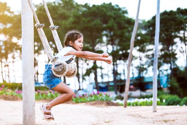 Fille enfant asiatique heureux s'amuser à jouer sur des balançoires en bois dans l'aire de jeux avec une nature magnifique Photo Premium