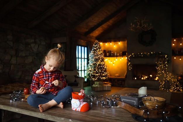 Fille enfant en bas âge au matin de noël, manger des bonbons d'un cadeau, assis sur une table en bois. Photo Premium