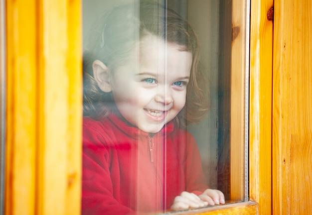 Fille enfant en bas âge regardant par la fenêtre. Photo Premium