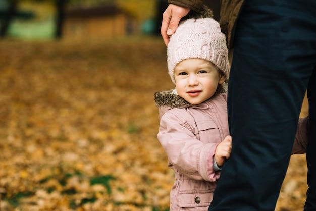 Fille enfant en bas âge se cachant derrière une jambe adulte Photo gratuit