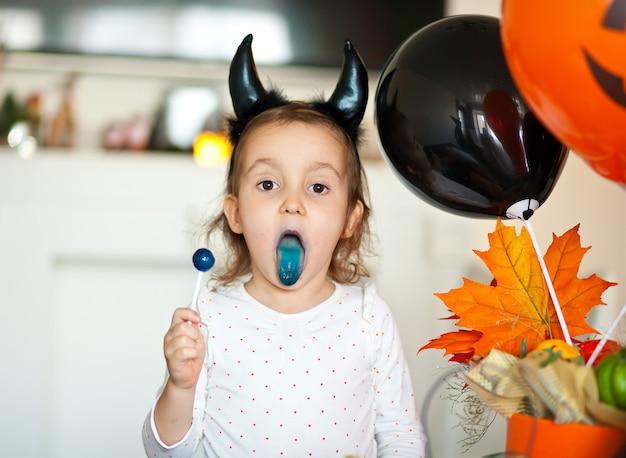 Fille Enfant Drôle En Costume Maléfique Pour Halloween Mangeant Des Bonbons Sucette Pop Et Amusez-vous. Photo Premium