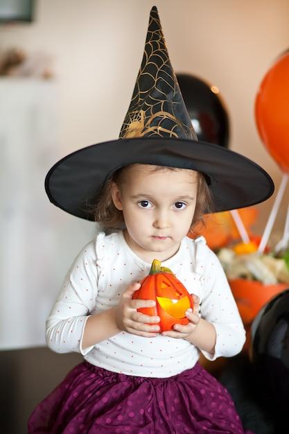 Fille Enfant Drôle En Costume De Sorcière Pour Halloween. Photo Premium