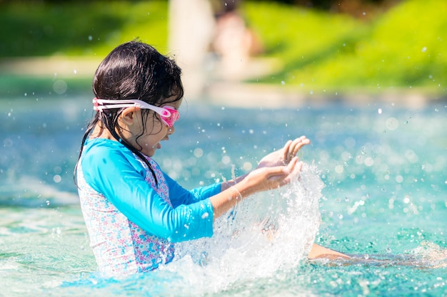 Fille enfant éclabousser sur la piscine avec heureux. Photo Premium