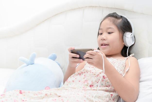 Fille enfant écoutant de la musique de smartphone. Photo Premium