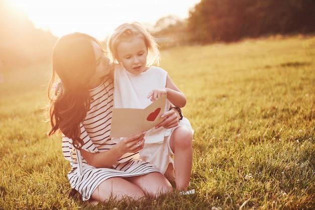 La Fille De L'enfant Félicite Sa Mère Et Lui Donne Une Carte Postale. Photo gratuit