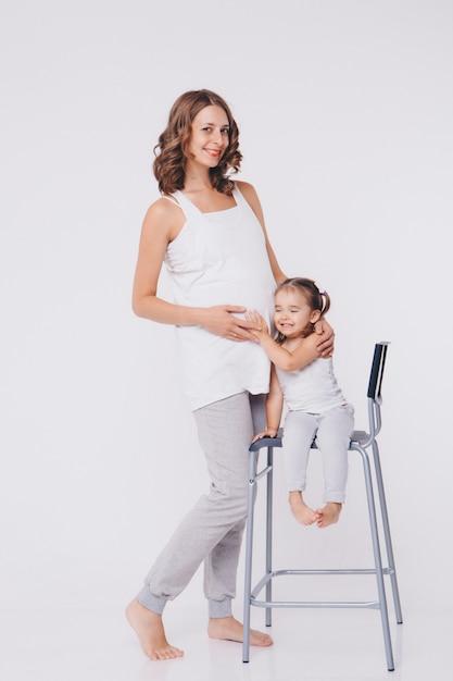 Fille enfant heureux étreignant le ventre de sa mère enceinte, sa grossesse et sa nouvelle vie. Photo Premium