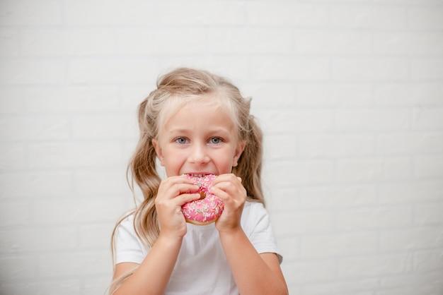 Fille Enfant Mignon Manger Beignet Glacé Rose Doux. Photo Premium