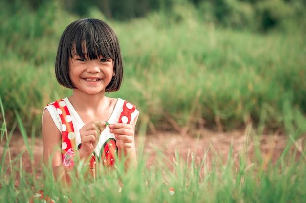 Fille d'enfants heureux souriant dans l'herbe sur les collines, pâturage vert flou sur fond Photo Premium
