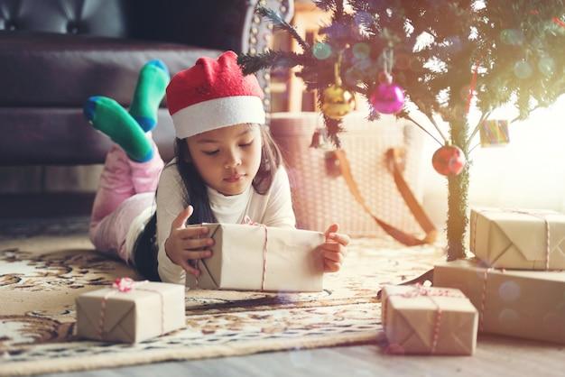 Fille D'enfants Avec Un Paquet Cadeau Dans La Journée De Noël Photo Premium