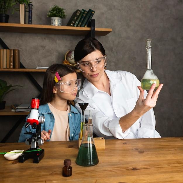 Fille Et Enseignant Faisant Des Expériences Scientifiques Avec Des Tubes à Essai Et Un Microscope Photo gratuit