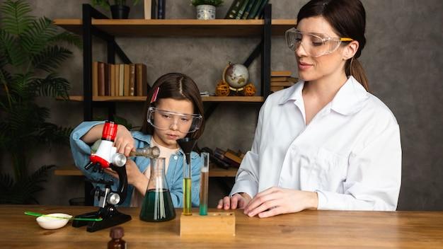 Fille Et Enseignante Faisant Des Expériences Scientifiques Avec Des Tubes à Essai Et Un Microscope Photo gratuit
