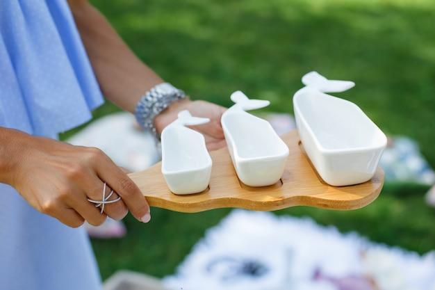 Fille avec un ensemble de saucisses vides blanches sur un plateau en bois sert un pique-nique Photo Premium