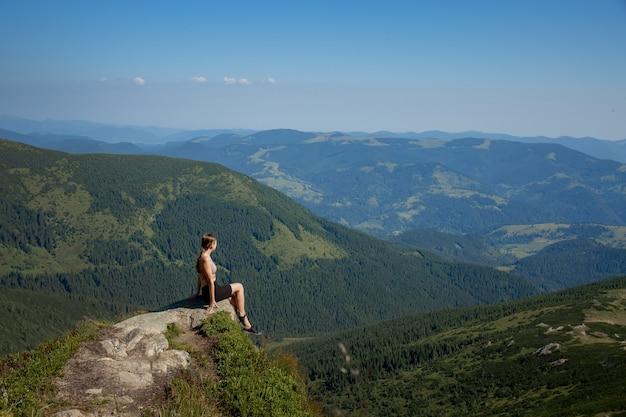 Une Fille Est Assise Au Bord De La Falaise Et Regarde La Vallée Du Soleil Et Les Montagnes. Photo Premium