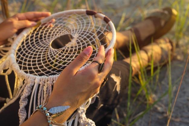 Une fille est assise sur l'herbe et tient un capteur de rêves Photo Premium