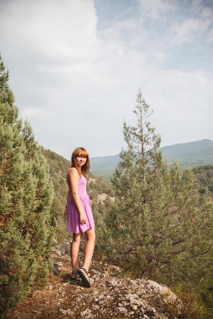 La fille est assise sur un rocher. le long de la rivière coule Photo Premium
