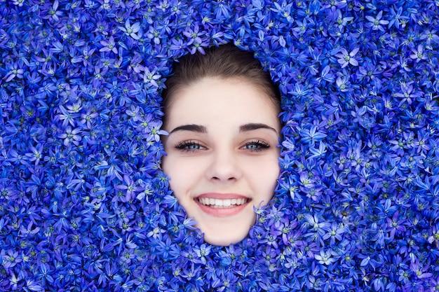 La fille est couverte de fleurs de printemps bleues, la fille regarde de dessous les fleurs. Photo Premium