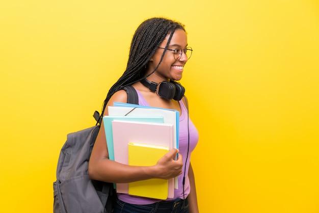 Fille étudiante adolescente afro-américaine avec de longs cheveux tressés sur un mur jaune isolé à la recherche du côté Photo Premium