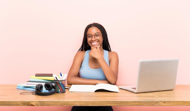 Fille étudiante adolescente afro-américaine avec de longs cheveux tressés sur son lieu de travail avec des lunettes et souriant Photo Premium