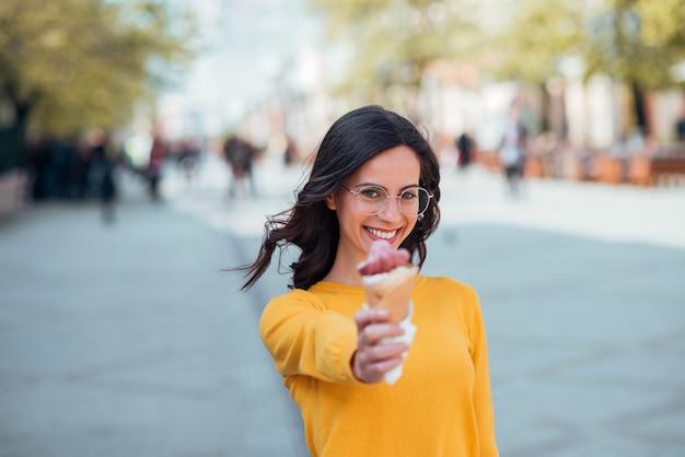 Fille étudiante avec cornet de crème glacée à l'extérieur. Photo Premium