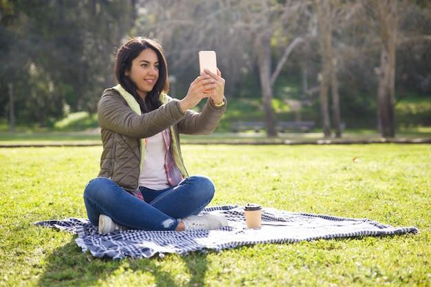 Fille étudiante excitée se reposer dans le parc et prendre des selfies Photo gratuit