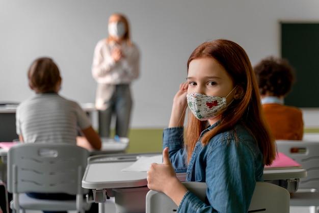 Fille étudiante Avec Masque Médical Fréquentant L'école Photo Premium