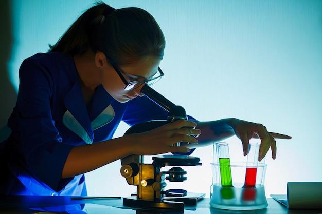 Fille étudiante à La Recherche Dans Un Microscope, Concept De Laboratoire Scientifique. Photo Premium