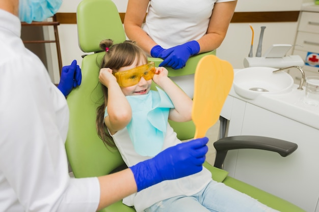 Fille excitée chez dentiste regardant miroir Photo gratuit