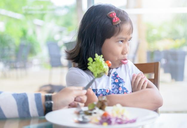 Fille avec une expression de dégoût contre les légumes Photo Premium