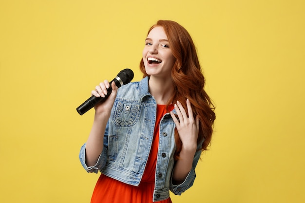 Fille expressive chantant avec un microphone, isolé fond jaune vif. Photo Premium