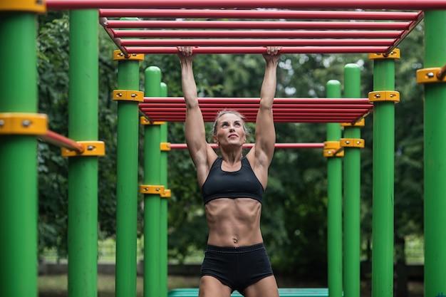 Fille faisant des exercices sur la barre horizontale, la femme est engagée dans une séance d'entraînement Photo Premium