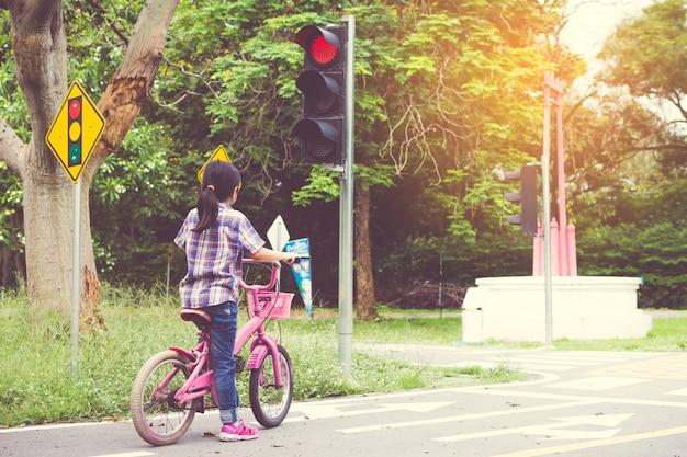 Fille fait du vélo dans le parc, le vélo s'arrête aux feux de circulation Photo Premium