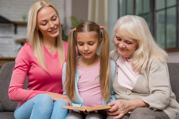 Fille Et Famille Assis Sur Un Canapé Et Lire Un Livre Photo gratuit