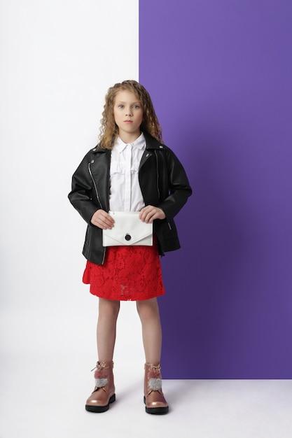 Fille Fashion Dans Des Vêtements élégants Sur Le Mur De Couleur. Vêtements Lumineux Automne Sur Les Enfants, Un Enfant Posant Sur Un Fond Rose Pourpre De Couleur. , Photo Premium