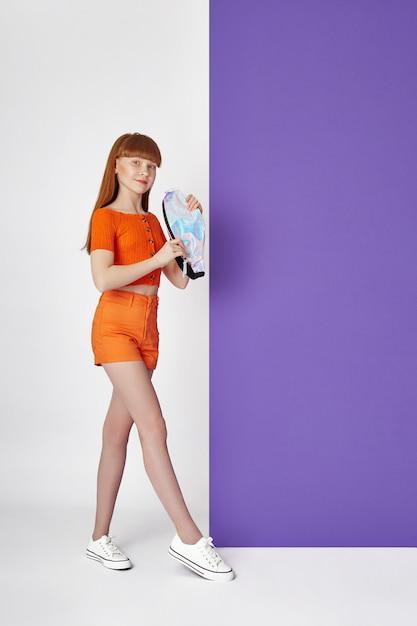 Fille Fashion Dans Des Vêtements élégants Sur Le Mur De Couleur. Vêtements Lumineux D'automne Sur Les Enfants Photo Premium
