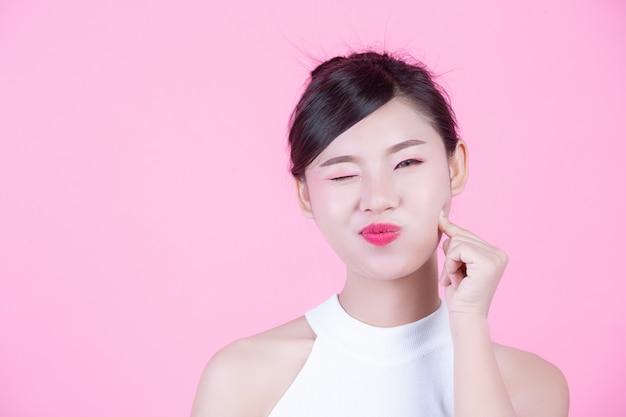 Fille fashion habiller avec des gestes de la main sur un fond rose. Photo gratuit