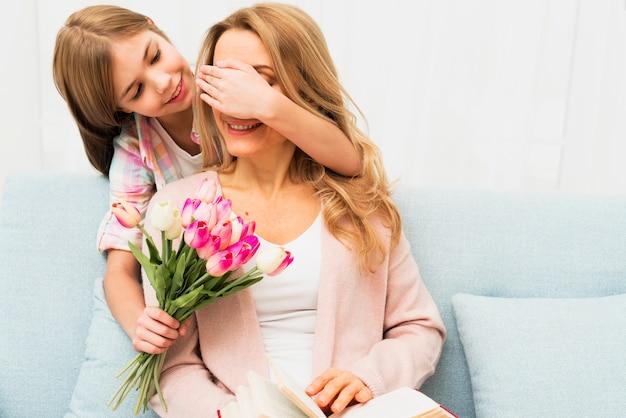 Fille fermant les yeux mère et donnant des fleurs surprises Photo gratuit