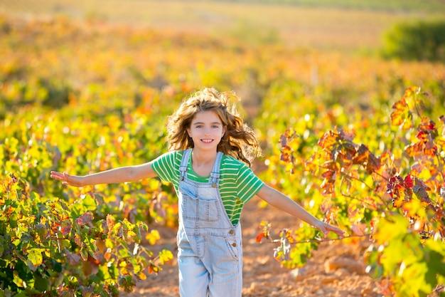 Fille de fermier enfant en cours d'exécution dans le champ de vigne en automne Photo Premium