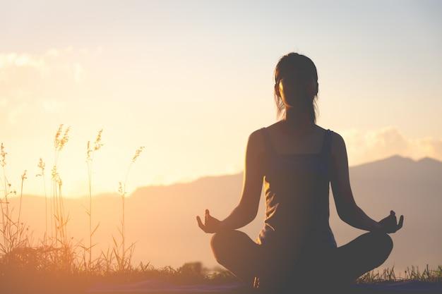 Fille De Fitness Silhouette Pratiquer L'yoga Sur La Montagne Avec La Lumière Du Soleil Photo Premium
