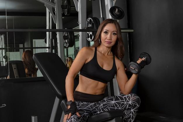 Fille Fitness Photo fille fitness soulevant des haltères dans la salle de gym pour