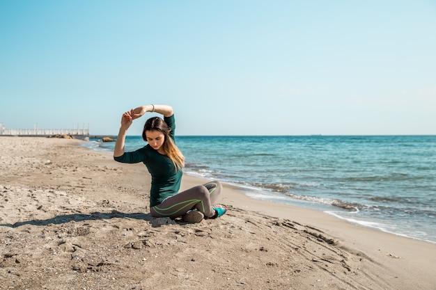 Fille En Fitness Sportswear Au Bord De La Mer à L'écoute Photo gratuit