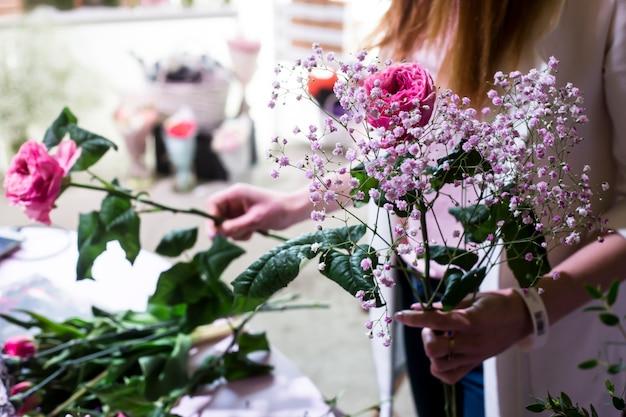 La Fille Fleuriste Crée Un Doux Bouquet De Gypsophile Et De Roses Photo Premium